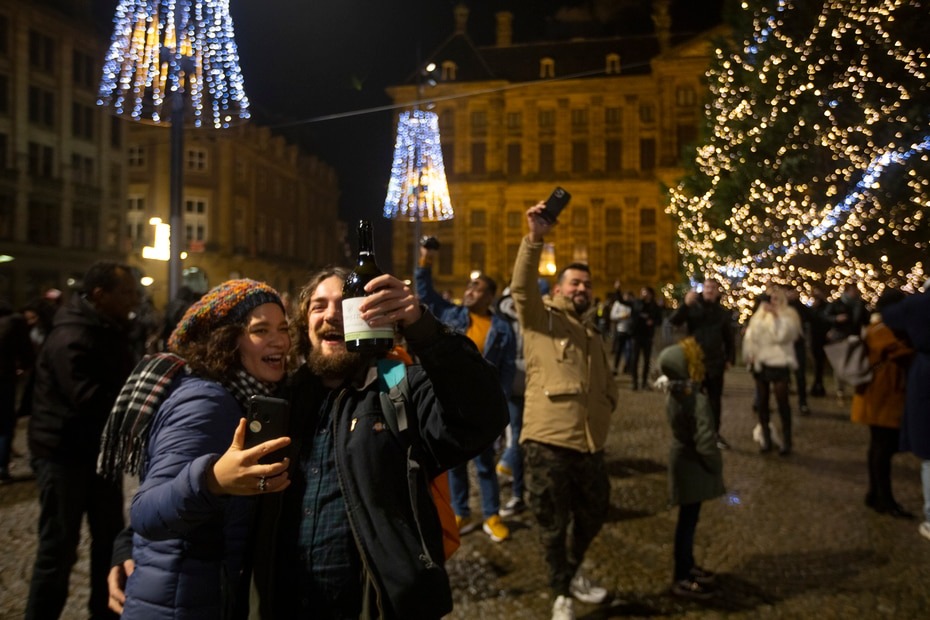 La gente celebra el Año Nuevo frente al Palacio Real, en la parte trasera, en Ámsterdam, Países Bajos, el viernes 1 de enero de 2021.