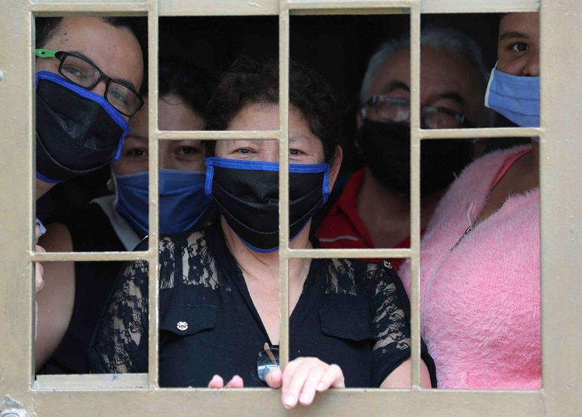 Una familia mira desde la ventana de su casa antes de recibir cajas de comida gratis durante la cuarentena para evitar la propagación del nuevo coronavirus en Bogotá, Colombia, el lunes 4 de mayo de 2020.  (AP)