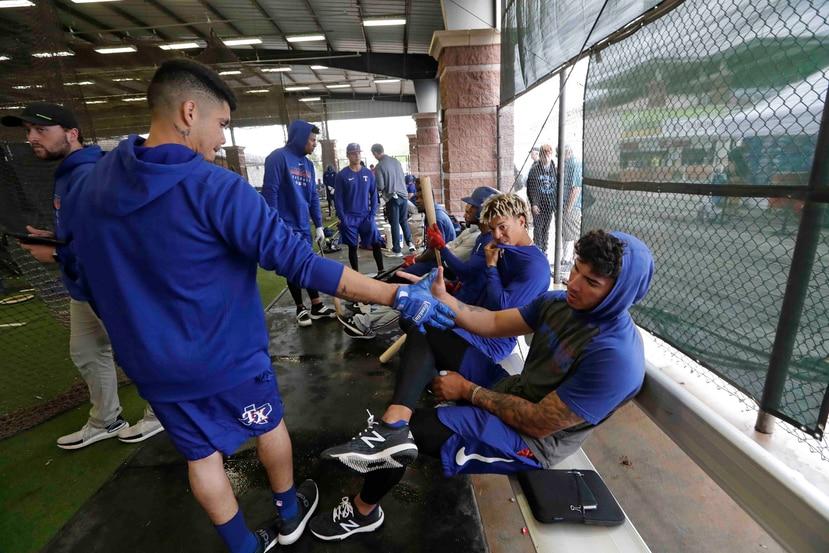 Jugadores de liga menor de los Rangers, como el campocorto de ascendencia boricua Chris Seise (derecha) y Kevin Mendoza, chocando manos durante una sesión del entrenamiento primaveral hace más de una semana. (AP / Elaine Thompson)