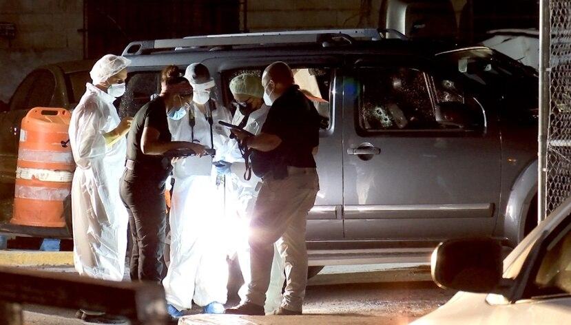 Las autoridades en la escena del crimen, donde se ve al fondo el auto baleado.