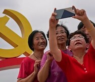 Women take a selfie with a communist party's logo on display at Tiananmen Square to mark the 100th anniversary of the founding of the ruling Chinese Communist Party in Beijing on Monday, July 5, 2021. Chinese leader Xi Jinping on Tuesday attacked calls from some in the U.S. and its allies to limit their dependency on Chinese suppliers and block the sharing of technologies. (AP Photo/Andy Wong)