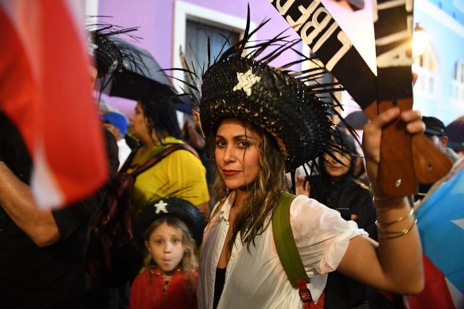 Esta participante de la marcha carga con dos machetes en madera y lleva puesta una pava color negra.