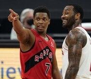 Kyle Lowry, de los Raptors de Toronto, charla con John Wall, de los Rockets de Houston, al concluir el partido del viernes.