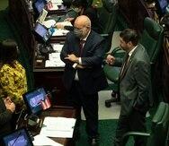 """Los portavoces de las delegaciones del PNP y PPD, Carlos """"Johnny"""" Méndez (al centro) y Ángel Matos (derecha), dialogan con otros legisladores durante la sesión legislativa."""