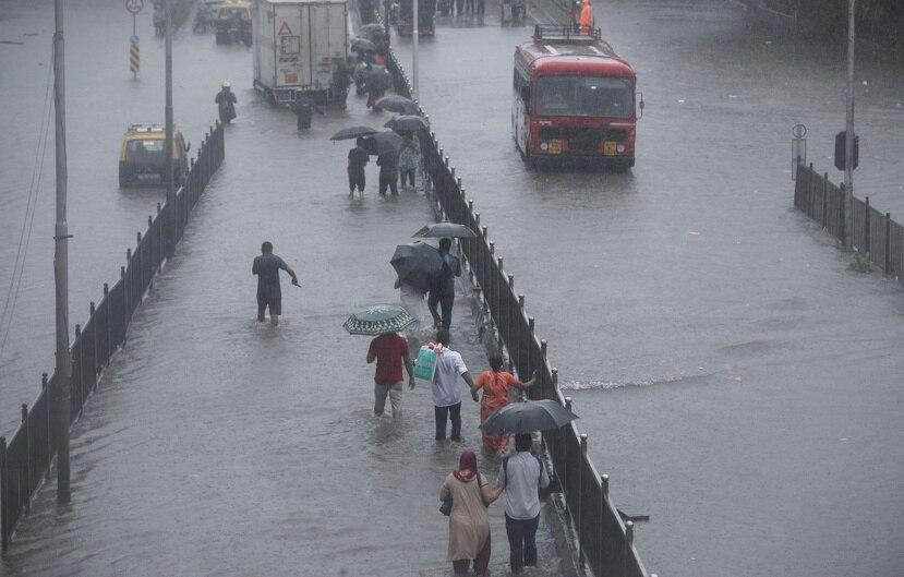 La gente camina por una calle inundada durante las fuertes lluvias en Mumbai, India.