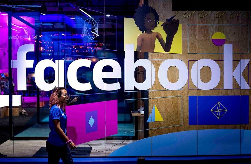 Una mujer pasando enfrente de una caseta con el logotipo de Facebook en la conferencia anual de programadores F8 de Facebook, en San Jose, California. (AP/Noah Berger)