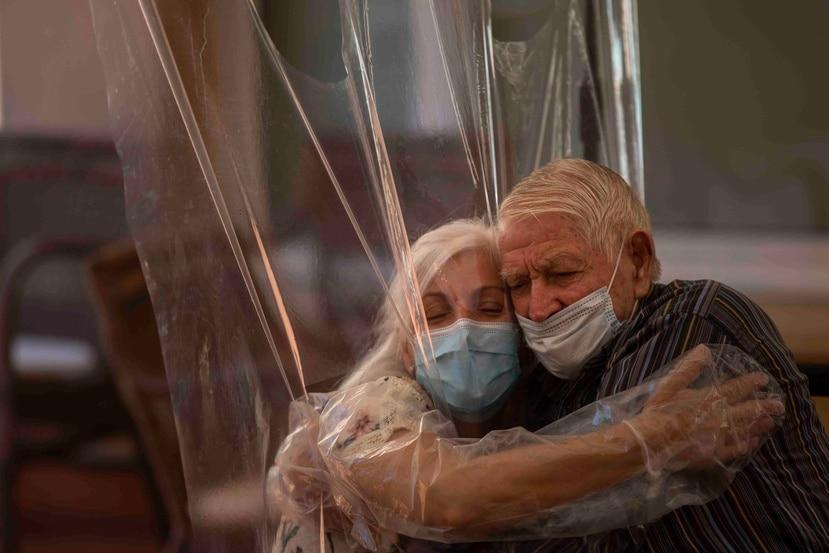 Dolores Reyes abraza a su padre José Reyes por primera vez en cuatro meses a través de una cortina de plástico en un asilo en Barcelona. (AP)