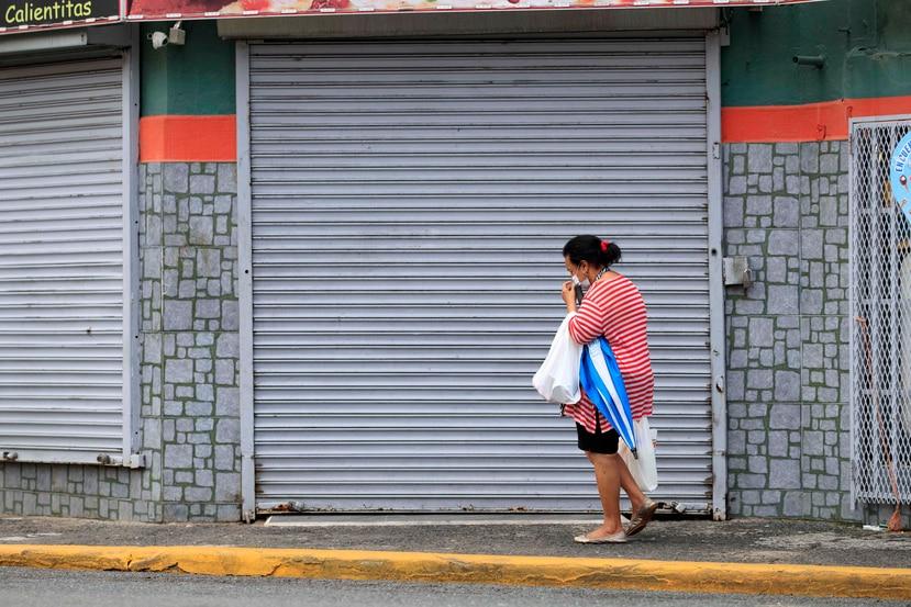 Una mujer pasa frente a un local cerrado en San Juan.