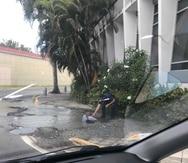 Foto del hombre sumergido dentro del hoyo, mientras otra persona le extiende una mano para sacarlo. La imagen fue tomada a las 11:52 a.m. el martes 2 de octubre por una joven que transitaba la avenida Roberto H. Todd. (Suministrada)