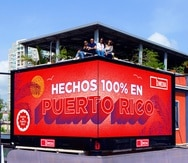 En la foto, la directora de la Junta de AHPR, Mónica Ponce; el cofundador y CEO de bMedia Group, Juan Casillas; la directora del comité de mercadeo de AHPR, Viviana Mercado y; la presidenta de la AHPR, Aysha Issa, sobre uno de los billboards que proyectará los anuncios de empresas locales.