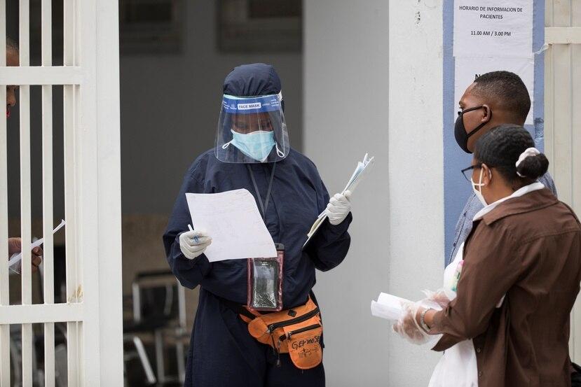 Personas solicitan información sobre un pariente que está ingresado por COVID-19 en el hospital Moscoso Puello, este martes en Santo Domingo.