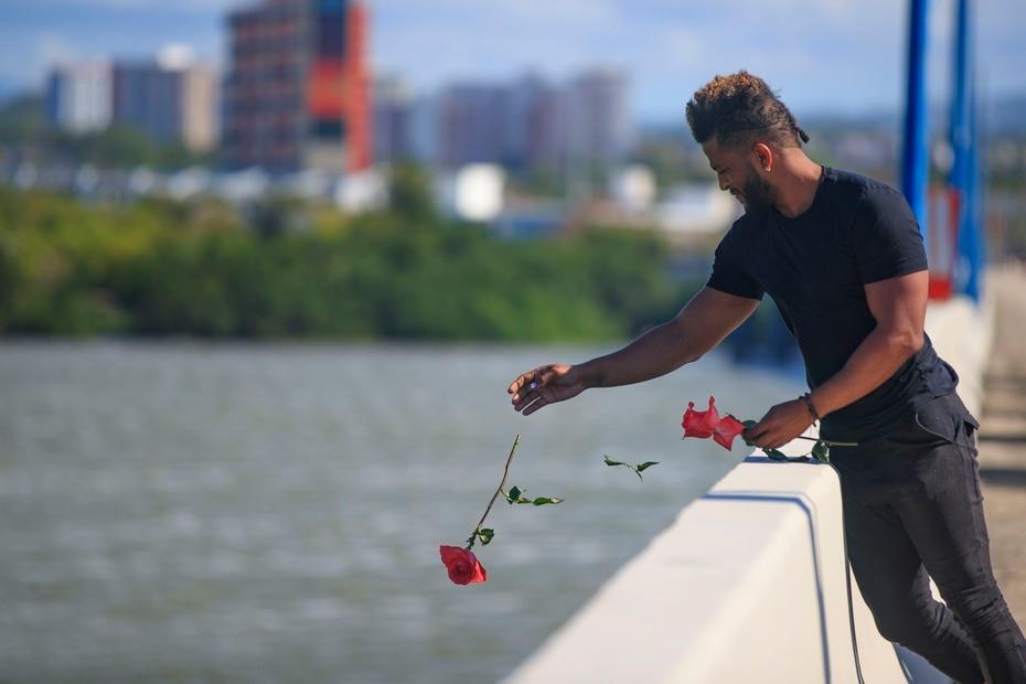 Un hombre suelta una flor en la laguna San José desde el puente Teodoro Moscoso, lugar donde fue encontrado el cuerpo de Keishla Rodríguez Ortiz.