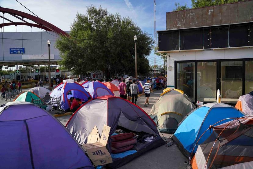 Fotografía del 30 de agosto de 2019 de personas en busca de asilo atravesando un campamento cerca del puente internacional Gateway en Matamoros, México. (AP / Veronica G. Cárdenas)