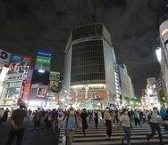 Personas con mascarillas para protegerse de la propagación del coronavirus caminan por el famoso cruce peatonal de Shibuya, en Tokio.