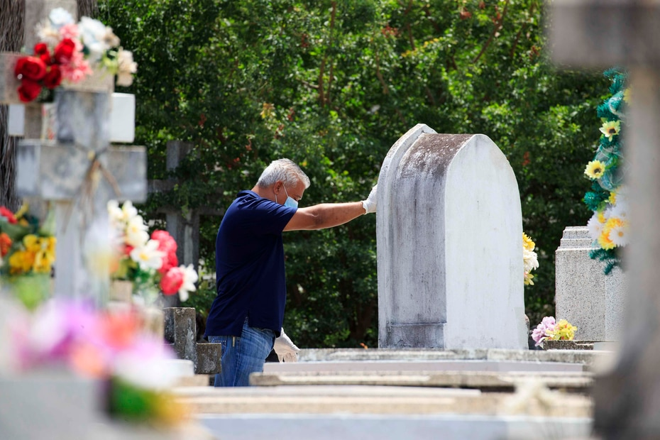 Un hombre ante una tumba en el cementerio Villa Palmeras en Santurce.