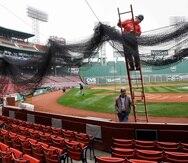 Foto de 2009 donde un personal coloca una malla protectora detrás del plato del Fenway Park en Boston. (AP)