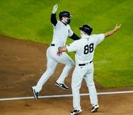 Clint Frazier y el coach Phil Nevin (88), de los Yankees de Nueva York, celebran el vuelacercas de Frazier durante la cuarta entrada del desafío del miércoles ante Toronto.