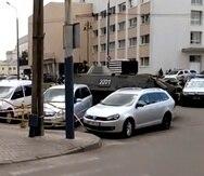 En esta imagen tomada de un video, una calle cortada por un vehículo blindado y un auto policial, a la derecha, después de que un hombre armado tomara como rehenes a unas 20 personas en la ciudad ucraniana de Lutsk, unos 400 kilómetros al oeste de Kiev.
