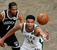 Kevin Durant (izquierda) de los Nets de Brooklyn defiende contra Giannis Antetokounmpo durante el tiempo extra del séptimo juego de la serie de segunda ronda de los playoffs de la NBA.
