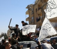 Members of the Hay'at Tahrir al-Sham, a Sunni Islamist militant group, wave the Taliban flags as they celebrate the Taliban takeover of Afghanistan, in the city of Idlib, Friday, Aug. 20, 2021.  The Taliban's takeover of Afghanistan is giving radical Islamic groups from Syria and the Gaza Strip to Pakistan and West Africa reason to celebrate. They see America's violence-marred exit from Afghanistan as an opportunity to regroup and reassert their ideology.  (AP Photo/Ghaith Alsayed)
