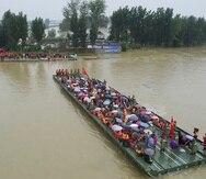 Rescatistas usan una barcaza motorizada para desalojar a residentes de un área rural inundada en Xinxiang, provincia de Henan, China, el viernes 23 de julio de 2021.