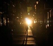Un policía patrulla junto a una mujer que camina en una calle de Nueva Orleans, el lunes 30 de agosto de 2021, luego de que la ciudad se quedó sin luz tras el paso del huracán Ida.