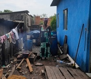 Lady Laurentino, de 74 años, posa para una fotografía junto a la hoguera que utiliza para cocinar, al lado de la entrada a su casa en la favela Jardim Gramacho, en Río de Janeiro, Brasil.