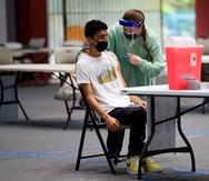 Un joven es vacunado contra el COVID-19 en el coliseíto Pedrín Zorrilla, en San Juan.