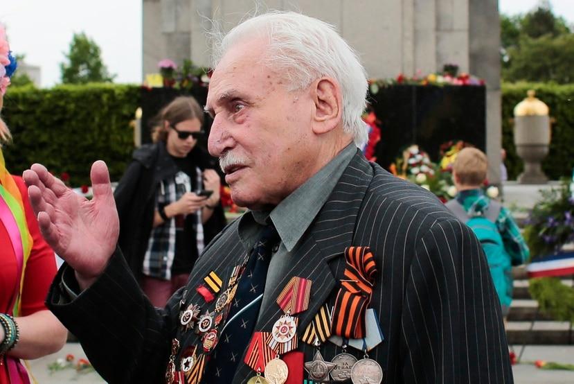 En esta imagen del viernes 8 de mayo de 2015, David Dushman, de 92 años, veterano de guerra de la ex Unión Soviética, habla con personas que ondean banderas ucranianas durante una ceremonia en el Monumento de Guerra Soviético en el Tiergarten, en Berlín, Alemania.