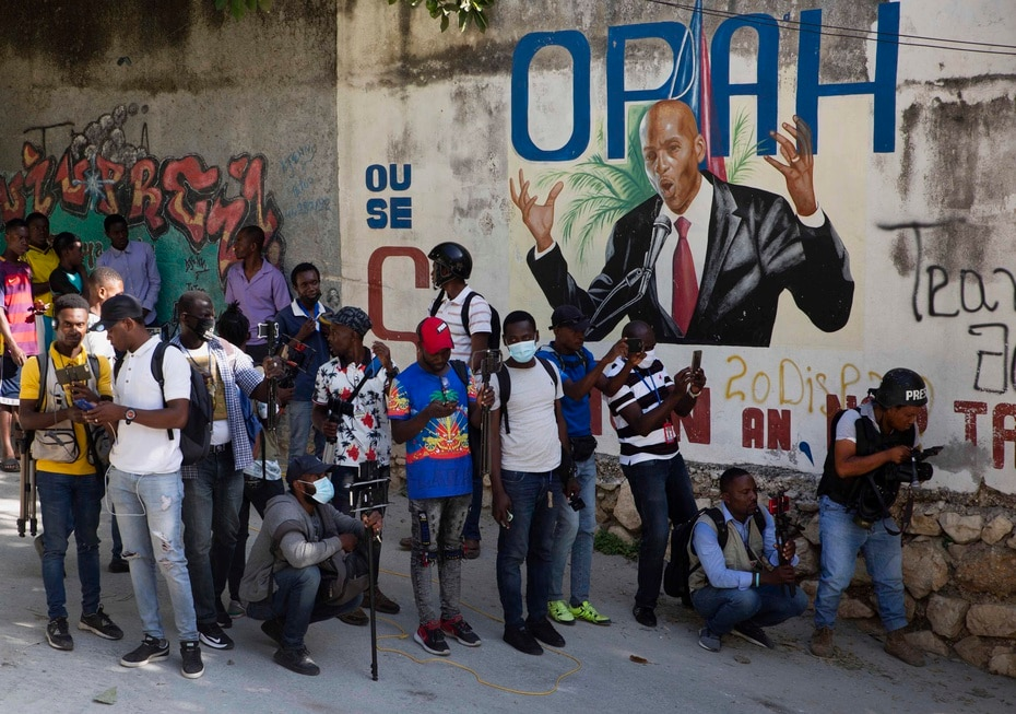 Periodistas aguardan cerca a la residencia del presidente asesinado, al fondo se observa un mural en honor al mandatario.