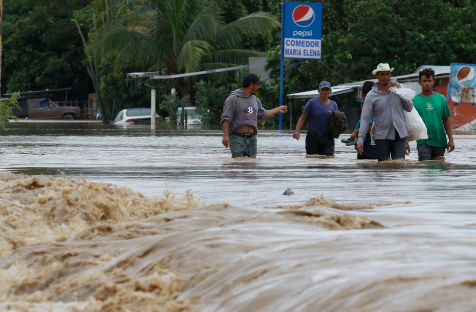 Varias personas pasan por un área inundada en la localidad de La Lima, Honduras.
