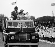 FILE - In this Wednesday, Oct. 15, 1977 file photo, Britain's Queen Elizabeth II and Prince Philip wave to young people at Nassau's Clifford Park after their arrival in Nassau, Bahamas. Buckingham Palace says Prince Philip, husband of Queen Elizabeth II, has died aged 99. (AP Photo/Kathy Willens, File)