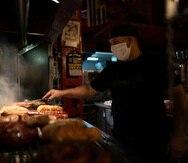 """Pedro Sosa cocina en una """"parrilla"""" tradicional en el restaurante """"El pobre Luis"""" en Buenos Aires, Argentina. (AP)"""