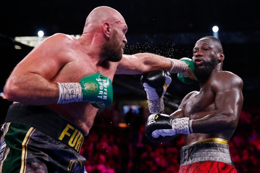 Tyson Fury conecta una izquierda a un agotado Deontay Wilder en los asaltos finales de su tercer combate titular.