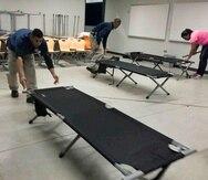 Empleados laboran en el refugio de la Escuela Vocacional William Rivera Betancourt en Canóvanas.