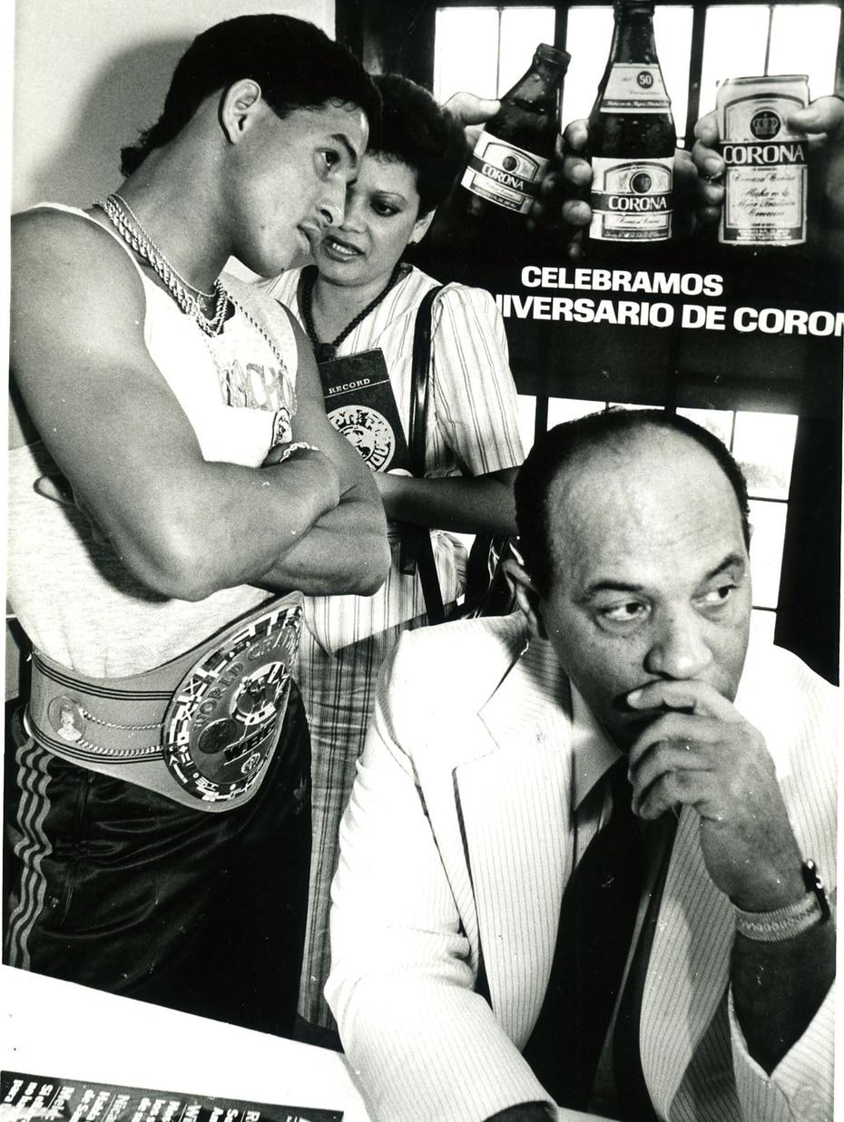 """Héctor """"Macho"""" Camacho, de brazos cruzados, con su correa de campeón Consejo Mundial de Boxeo (CMB) y sus vistosas prendas, durante una conferencia de prensa el 15 de noviembre de 1985, relacionada a su combate con Rafael Solís. Sentado, el exlanzador de"""