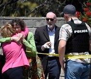 Dos personas se abrazan mientras otra habla con un diputado del alguacil del condado de San Diego fuera de la sinagoga de Jabad de Poway, el sábado 27 de abril de 2019, en Poway, California. Un hombre abrió fuego dentro de la sinagoga cerca de San Diego m