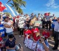El pastor Arturo Ramirez, derecha, ora durante una protesta el martes 13 de julio de 2021, en Southernmost Point de Key West, Florida. (Rob O'Neal/The Key West Citizen vía AP)
