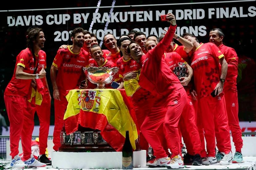 Rafael Nadal utiliza un teléono móvil para tomarse un selfie junto a los integrantes del equipo campeón de España. (AP / Manu Fernández)