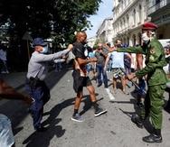 """HAB15. LA HABANA (CUBA), 11/07/2021.- Policías arrestan a un hombre cuando personas se manifiestan hoy, en una calle en La Habana (Cuba). Cientos de cubanos salieron este domingo a las calles de La Habana al grito de """"libertad"""" en manifestaciones pacíficas, que fueron interceptadas por las fuerzas de seguridad y brigadas de partidarios del Gobierno, produciéndose enfrentamientos violentos y arrestos. EFE/Ernesto Mastrascusa"""