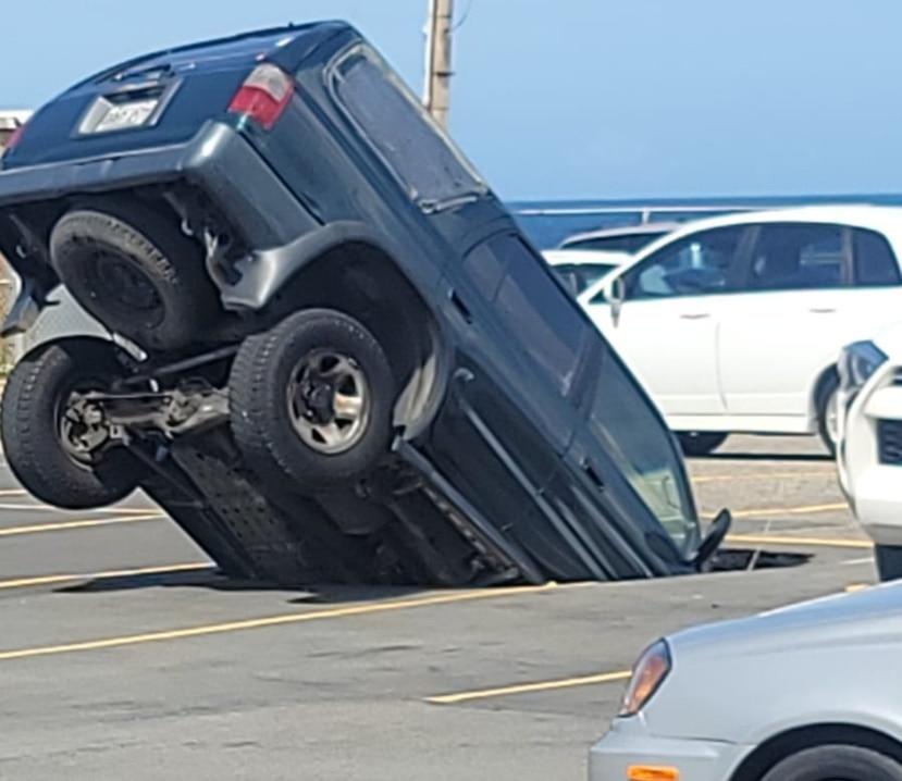 Una guagua cae en un socavón en el estacionamiento de un centro comercial en Arecibo.