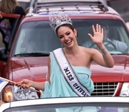 Holding the Puerto Rican and Vieques flags, Miss Universe Denise Quinones waves to well-wishers during a caravan upon her arrival in San Juan, Puerto Rico Monday July 16, 2001. (AP Photo/Gerald Lopez-Cepero)