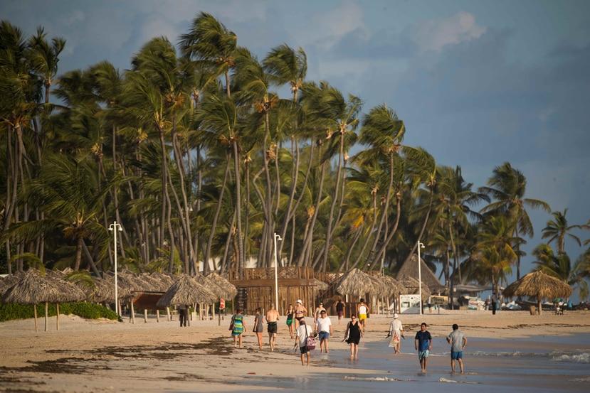 Turistas caminan por playa Bávaro en Punta Cana. (EFE)