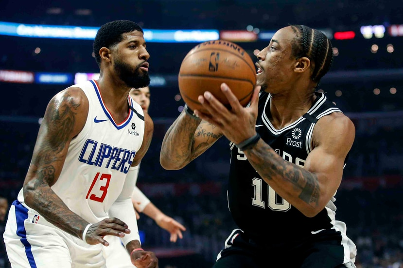 El jugador de los Spurs de San Antonio DeMar DeRozan (10) intenta pasar el balón ante la presión de su rival de los Clippers de Los Ángeles Paul George (13). (AP)
