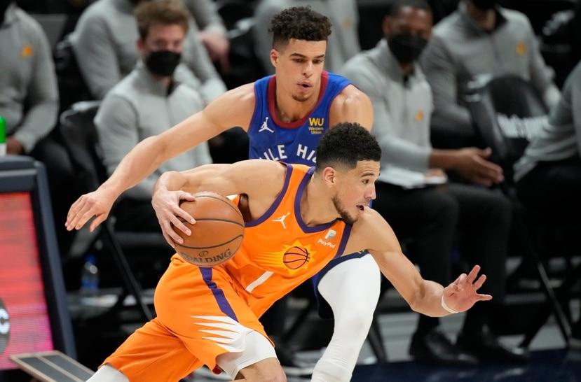 Devin Booker, de los Suns de Phoenix, driblea frente a la defensa de Michael Porter Jr., de los Nuggets de Denver.