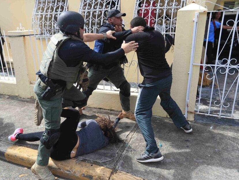 Dos agentes de la Policía estatal intentan detener a un manifestante mientras una mujer busca no ser pisoteada.