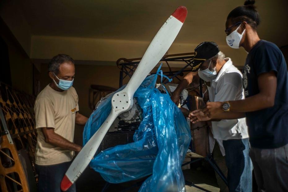 Adolfo Rivera, a la izquierda, quita el plástico protector de la avioneta.
