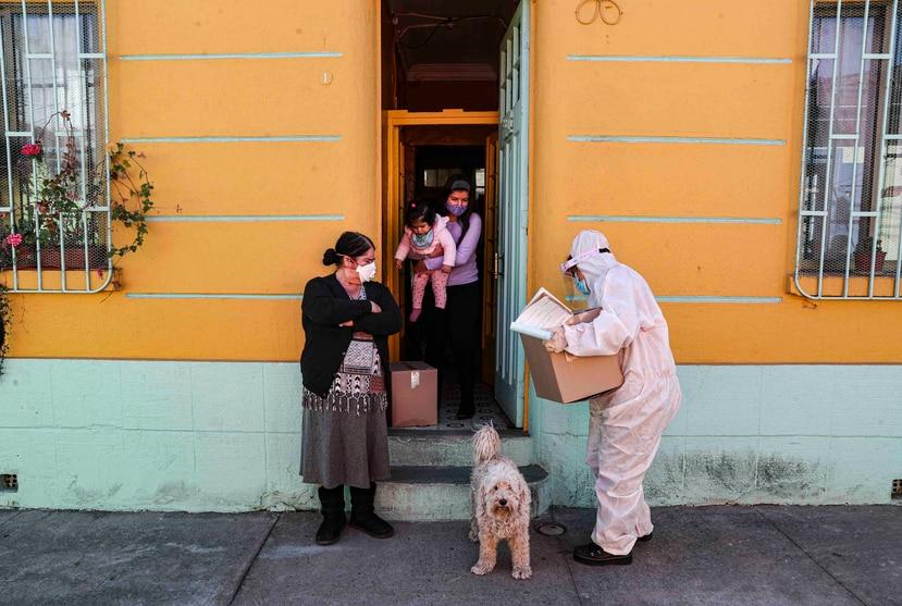 Un trabajador del gobierno de Chile entrega una caja de comida a ciudadanos. (AP)