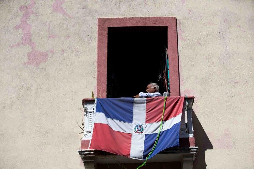 Un anciano observa desde su balcón, donde tiene colgada una bandera dominicana. (EFE)
