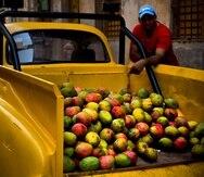 Un vendedor de mangos espera por clientes al lado de su Chevrolet clásico que  convirtió en camioneta, en La Habana, Cuba.